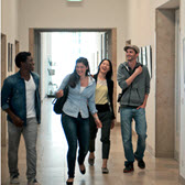 Four international students walk down a corridor and chat.
