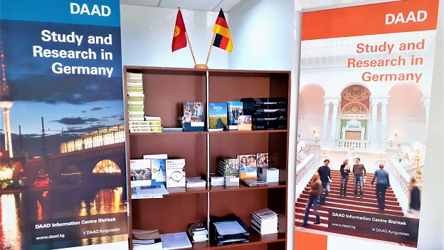 A shelf with brochures flanked by roll-ups with DAAD logo.